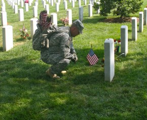 Memorial Day: A soldier pauses while placing flags on the graves Arlington National Cemetery in Virginia in preparation for Memorial Day ave the military cemetery.